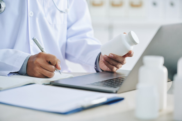 unrecognizable female doctor with laptop holding medication writing prescription 1098 17464